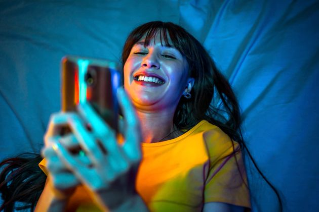 Young cheerful woman is using mobile phone in bed at