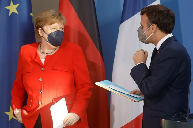 German Chancellor Angela Merkel and French President Emmanuel Macron talk after giving a press conference...