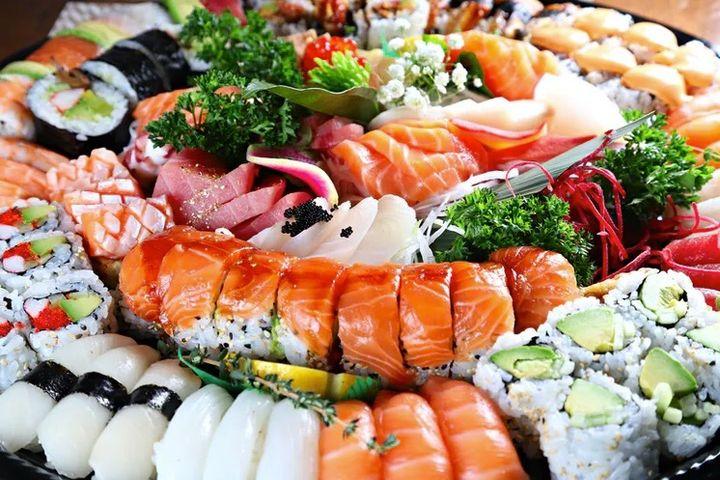 Bandeja con sashimi, sushi y rollos maki.