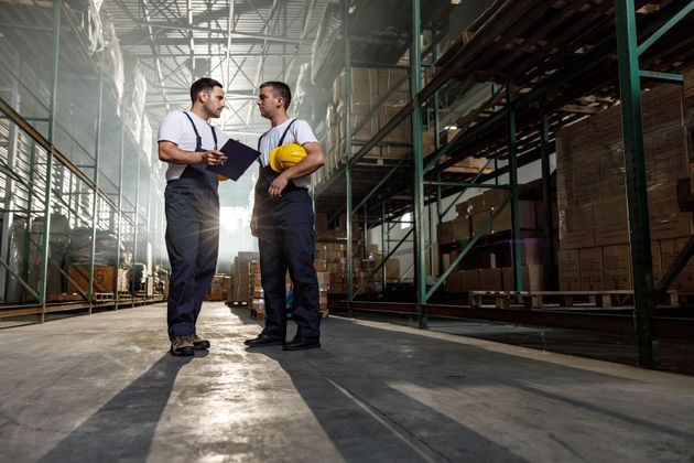 Young warehouse workers communicating while going through checklist together. Copy