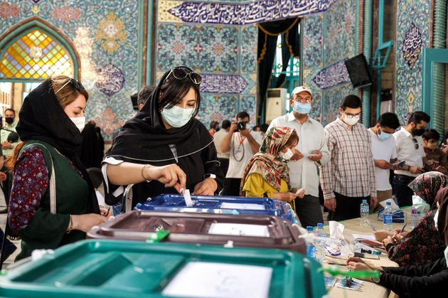 A woman casts her ballot as she votes at a polling station polling station in Iran's capital Tehran on...