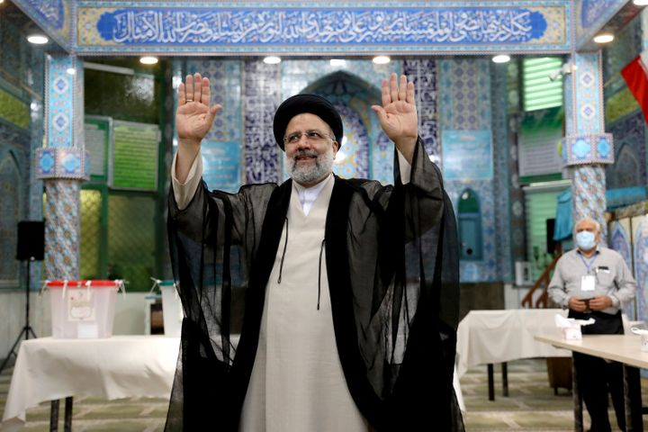 Ebrahim Raisi waves to the media after casting his vote at a polling station in Tehran, Iran Friday, June 18, 2021. (AP Photo