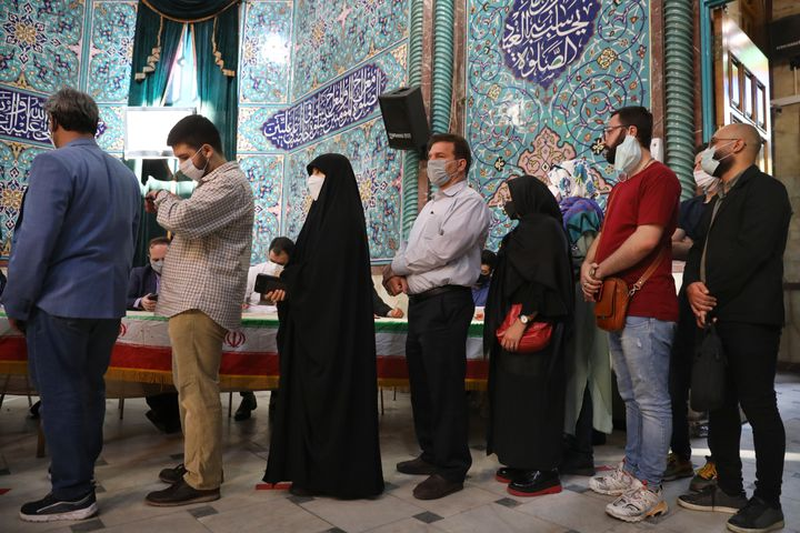 Voters queue at a polling station during the presidential elections in Tehran, Iran, Friday, June 18, 2021. Iranians voted Fr