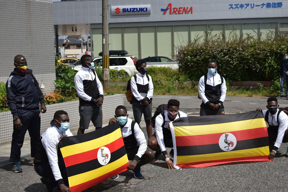 Members of the Uganda Olympics team pose for a photo call as they arrive at a hotel in Izumisano city,...