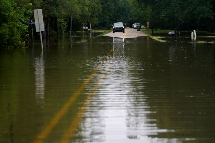 A car stops in front of neighborhood flooding after Tropical Storm Claudette passed through, in Slidell, La., on Saturday.