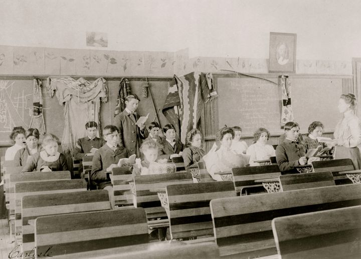 Students are seen reading in a classroom at the Indian Industrial School, in Carlisle, Pennsylvania, in 1901. The boarding sc