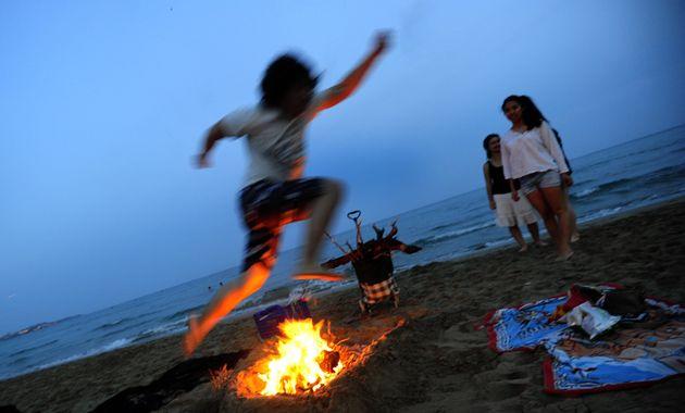 Gente saltando hogueras en la noche de San Juan, en