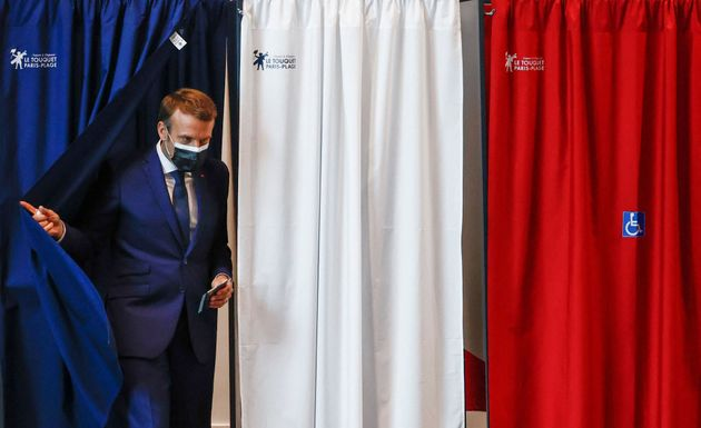 TOPSHOT - French President Emmanuel Macron leaves the polling booth before he votes at the polling station...