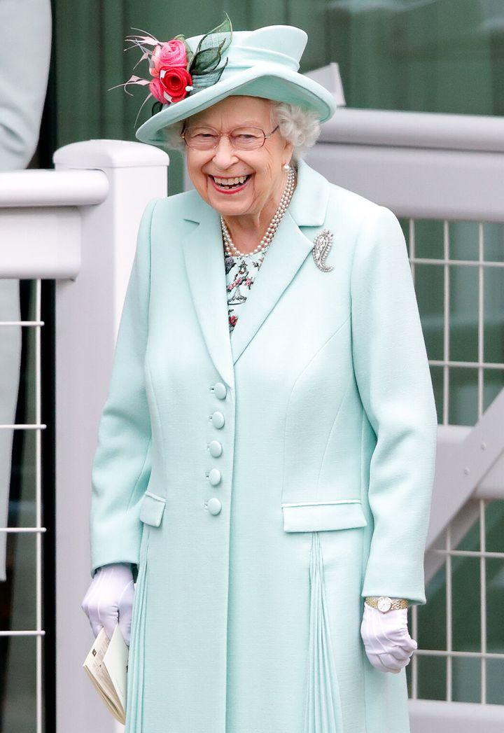 Queen Elizabeth II, wearing her Cartier diamond Palm Leaf Brooch, which belonged to Queen Elizabeth, the Queen Mother) holds