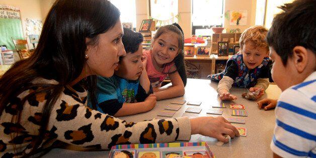 BOULDER, CO - MARCH 30:  Preschool teacher Fernanda Perez Chaves, {cq}, left, plays a memory game called 'I Never Forget a Fa