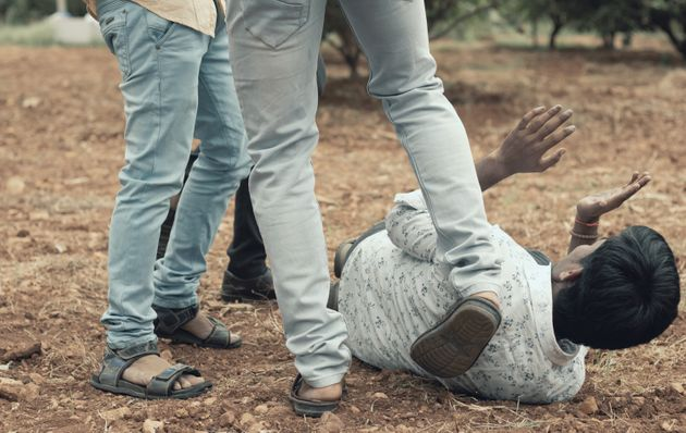 Concept of mob lynching - Group of people bullying, kicking a man - Close up of young adult males hitting...