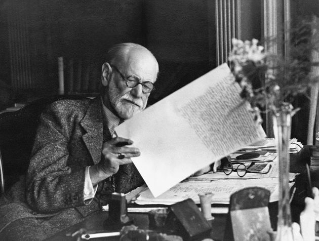 Sigmund Freud, 1856-1939, Austrian psychiatrist, in the office of his Vienna home looking at a