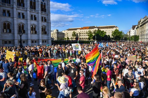 Participants gather near the parliament building in Budapest on June 14, 2021, during a demonstration against the Hungarian government's draft bill seeking to ban the