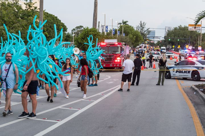 Parade participants walk away as police investigate the scene where a pickup truck drove into a crowd of people at a Pride pa