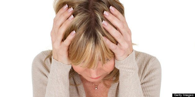 mature woman with her head in her hands as depression concept isolated on white background