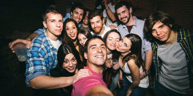 Smiling friends taking selfie in nightclub