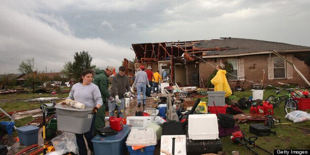 MOORE, OK - MAY 23: Volunteers help a co-worker to salvage belongings from her home after it was destroyed by a tornado May 23, 2013 in Moore, Oklahoma. The two-mile wide EF5 tornado touched down May 20 killing at least 24 people and leaving behind extensive damage to homes and businesses. U.S. President Barack Obama promised federal aid to supplement state and local recovery efforts. (Photo by Scott Olson/Getty Images)