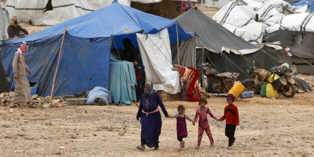 Syrian refugees stuck between the Jordanian and Syrian borders waiting to cross into Jordan, walk at a camp, after a group of