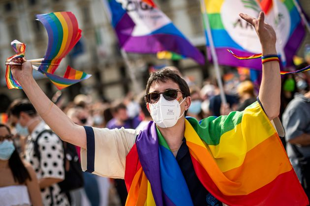 PIAZZA CASTELLO, TURIN, ITALY - 2021/06/05: A demonstrator holds rainbow flags during a LGBT demonstration...
