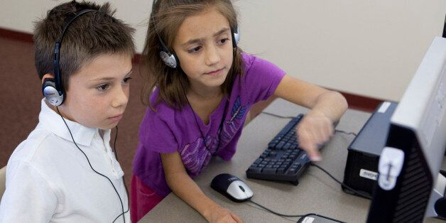 PHOENIX, AZ - OCTOBER 11: Ella Richardson helps Aidan Sawyer during class on October 11, 2013 at Horseshoe Trails Elementary School in Phoenix, AZ.  Formal keyboarding instruction at the school began this year for second-graders, in anticipation of the Common Core curriculum. (Photo by David Jolkovski for The Washington Post via Getty Images)