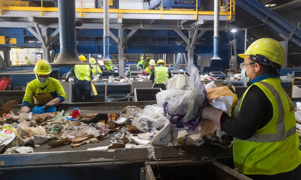 Workers remove non-recyclable plastics from cardboard at Republic Services in Anaheim, California, on April 15, 2021.