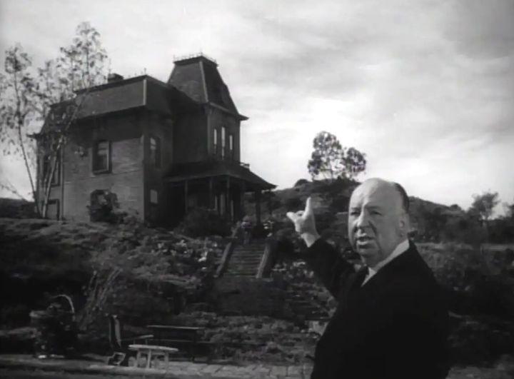 Alfred Hitchcock ante el motel de Psicosis, imagen perteneciente al tráiler oficial de la película.