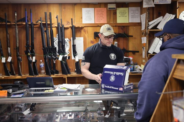A customer is assisted with a gun purchase at a store in Tinley Park, Illinois.About 42% of last year's gun sale denial
