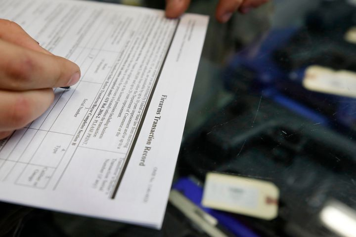 A customer fills out a background check form at a store in Orem, Utah. More than 300,000 people were prevented from purchasin