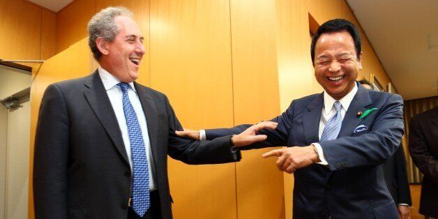 US Trade Representative Michael Froman (L) is greeted by his Japanese counterpart Akira Amari (R) prior to their talks over d