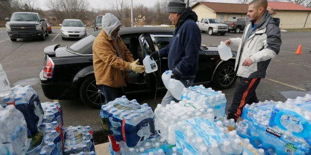 Volunteers load a vehicle with bottled water at Our Lady of Guadalupe Church, Friday, Feb. 5, 2016 in Flint, Mich. Michigan G