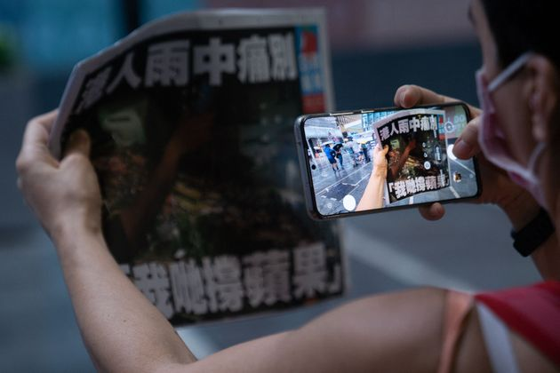 A woman takes a photo of the Apple Daily newspaper's final edition in Hong Kong's Central district on...
