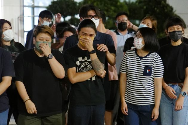 Apple Daily journalists get emotional after thanking supporters gathered outside their office in Hong...