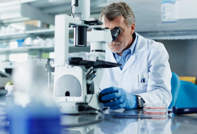 Scientist looking through microscope in research