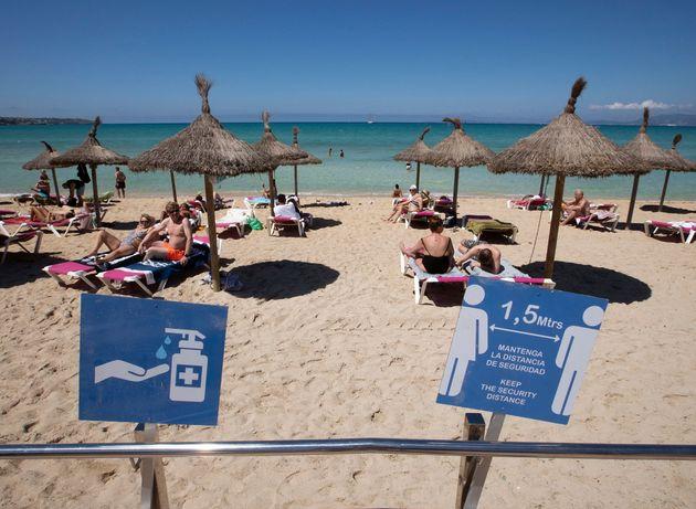 Tourists sunbathe at Palma Beach in Palma de Mallorca on June 7, 2021. - (Photo by JAIME REINA / AFP)...