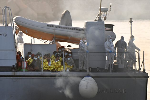 Migrants warmed by emergency blankets (Front L) arrive on a boat of the Italian Guardia Di Finanza law...