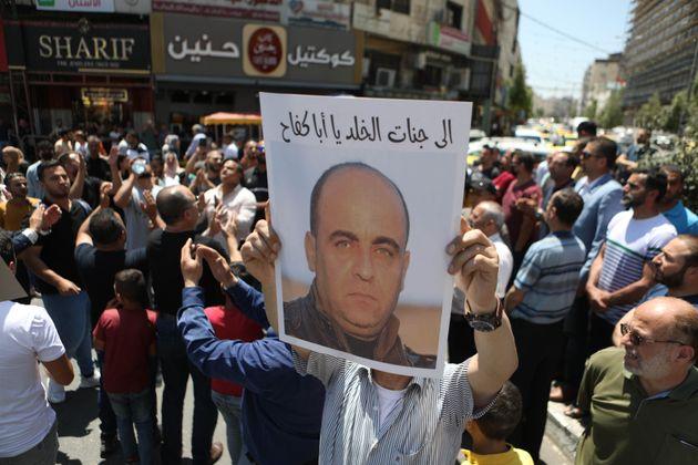 Un manifestante porta una foto de Nizar Banat, ayer, en