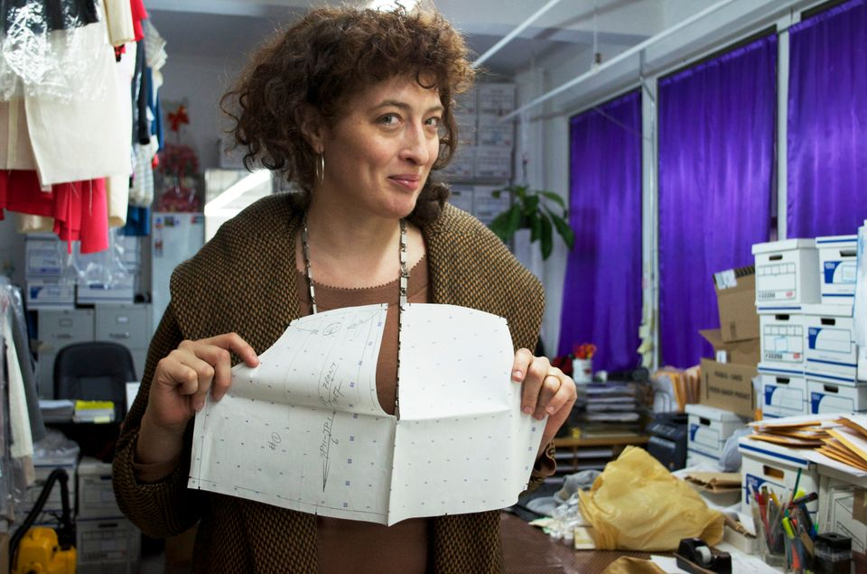 Designer Lizzy Seklir holds up a pattern for the front of a halter top in her Manhattan-based manufacturing office. All her c
