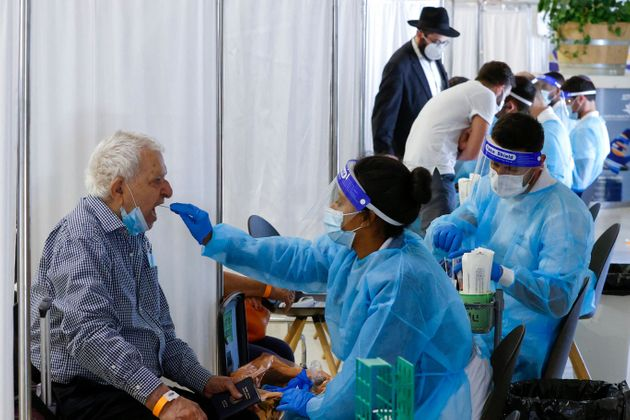 Israelis and vaccinated tourists get tested for COVID-19 upon arrival to Israel's Ben Gurion airport...