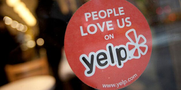 The Yelp Inc. logo is displayed in the window of a restaurant in New York, U.S., on Thursday, March 1, 2012. Yelp Inc., the s