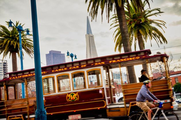 A motion blurred Cable Car on The Embarcadero near Washington street the Transamerica Pyramid background...