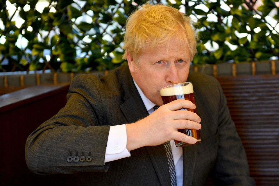 Boris Johnson, sips a pint of beer at a pub in