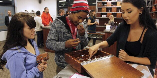 Morgan McKee (R) helps Juliano Hamana (C) and Jayme Jennings (L) browse samples at Shango Cannabis shop on first day of legal