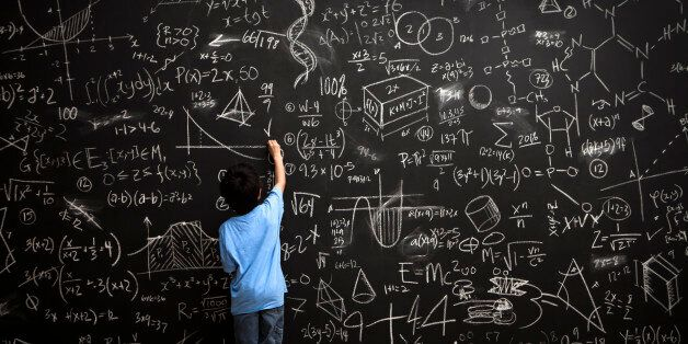 A young boy stands drawing on a huge chalkboard filled with mathematical equations