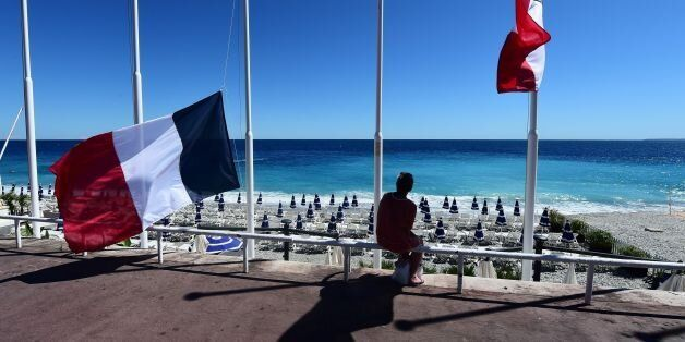 A woman sits under French flags lowered at half-mast in Nice on July 15, 2016, following the deadly Bastille Day attacks. A