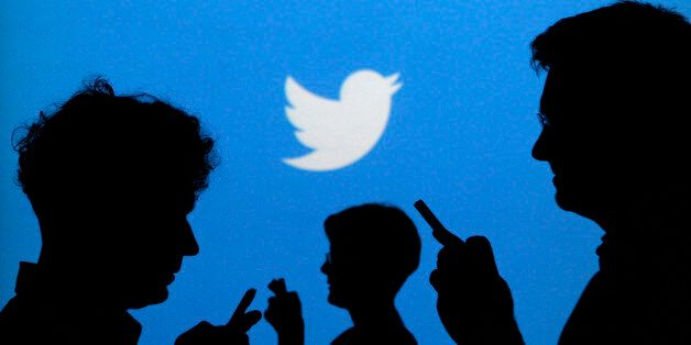 People holding mobile phones are silhouetted against a backdrop projected with the Twitter logo in this illustration picture
