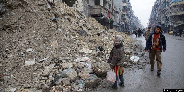 ALEPPO, SY  - FEBRUARY 13: A Syrian girl pauses in awe of the destruction wrought by an Assad regime bombing run on a busy st