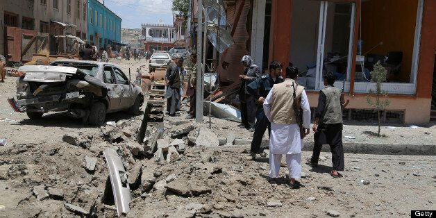 Afghan officials and bystanders are pictured at the site of a roadside bomb blast in Ghazni province on July 3, 2013. The bla