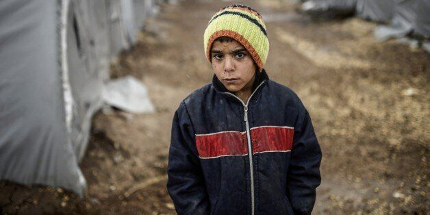A Kurdish refugee boy stands during a rainy day at the Rojova Camp, in Suruc, a rural district of Sanliurfa Province, on Octo