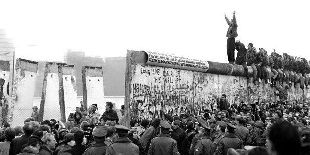 BERLIN - CIRCA NOVEMBER 1989:  People gather near a part of the Berlin Wall that has been broken down after the communist Ger