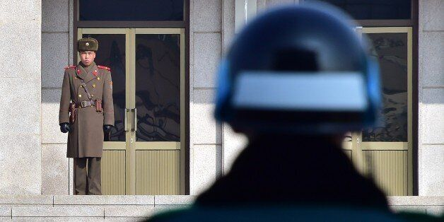 A North Korean soldier (L) and a South Korean soldier (R) stand opposite each other at the truce village of Panmunjom in the